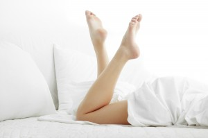 Woman legs on the bed with white bed clothes