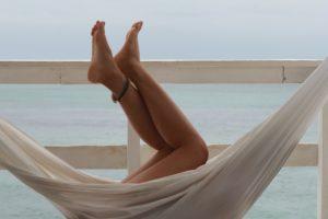 Jambes de femme dans un hamac face à la mer